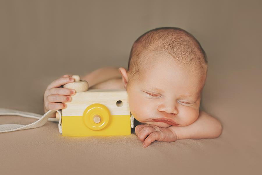 ședință foto de nou născut care doarme sprijinit de un aparat foto